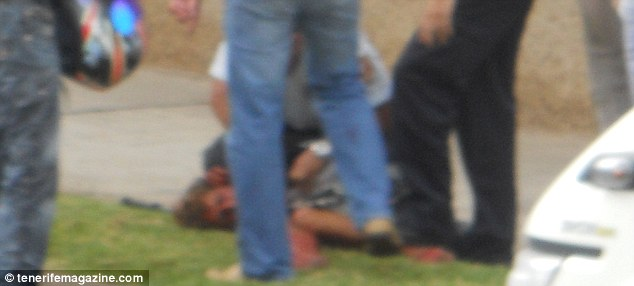 Horror: The man lies on the ground after being tackled by security guards as he ran down the street