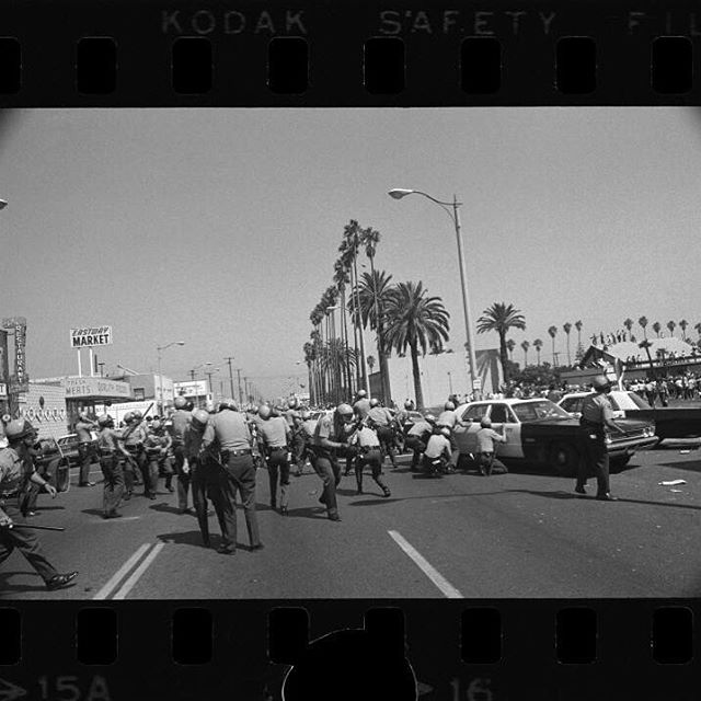 Title: Rioting following Chicano Moratorium Committee antiwar protest Barrage--Sheriffs' deputies duck and crouch behind cars on Whittier Blvd. near Indiana St., to avoid a barrage of rocks and bottles  Date: August  17, 1970 #FTP